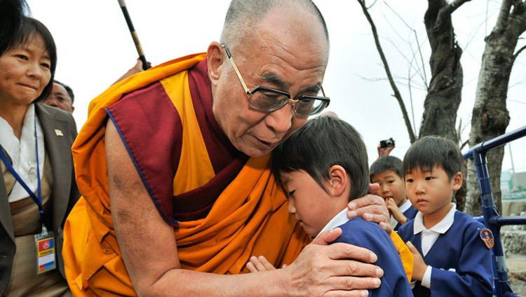 His Holiness the Dalai Lama comforting a young survivor during his visit to the Tsunami devastated region of Sendai, Japan on November 5, 2011. (Photo by Tenzin Choejor/OHHDL)