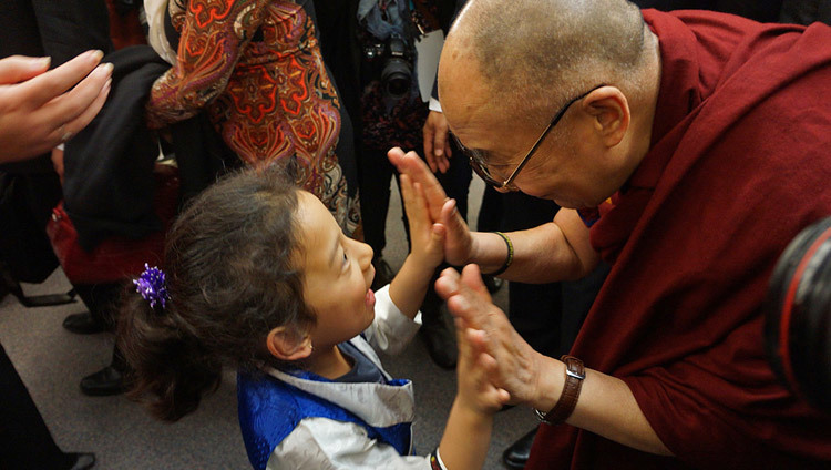 His Holiness the Dalai Lama greeting a young girl during his visit to Vancouver, BC, Canada on October 22, 2014. (Photo by Jeremy Russell/OHHDL)