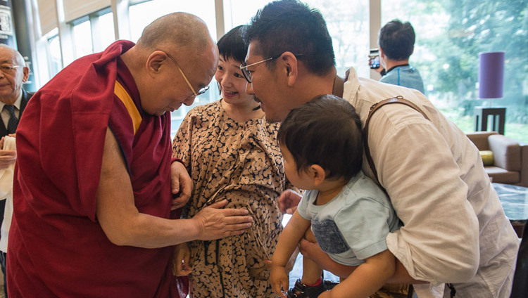 His Holiness the Dalai Lama blessing an expectant mother as he leaves his hotel in Narita on his way to Osaka, Japan on May 9, 2016. (Photo by Tenzin Choejor/OHHDL)